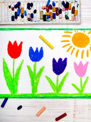 Photo of colorful hand drawing: beautiful tulip flowers and sun on white wooden background.