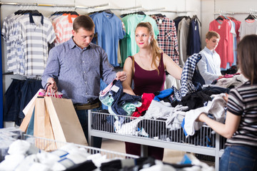 Positive family choosing clothes a half-off sale