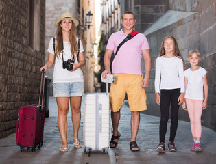 Glad family of tourists walking with suitcases