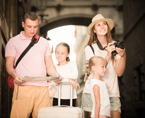 Positive family with children using map and photographing