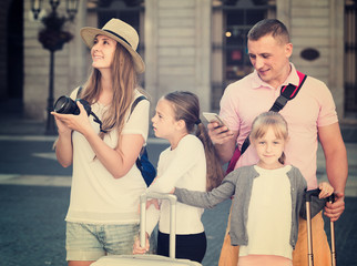 parents with two kids using smartphone and photographing sights during their travel