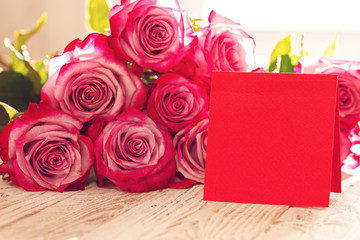 Blank red paper card for Valentines or mother or woman day. Background with pink roses