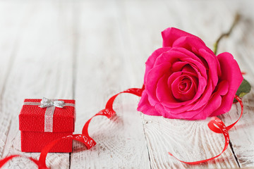 Beautiful Pink rose with gift box, holiday present on white wooden background.