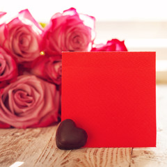 Blank red paper card with heart chocolate for Valentines or mother or woman day. Background with pink roses. Square
