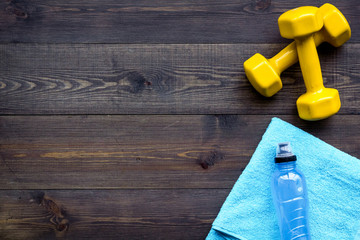 Fitness equipment. Dumbbells, water on dark wooden background top view copy space