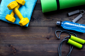 Fitness equipment. Jump rope, dumbbells, expander, mat, water on dark wooden background top view copy space