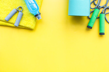 Fitness background. Equipment for gym and home. Jump rope, mat, water, expander, towel on pastel yellow background top view copy space