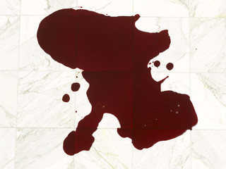 Puddle of red viscous fluid on white marble tiles