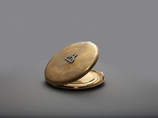 Gold colour face powder compact mirror, grey background