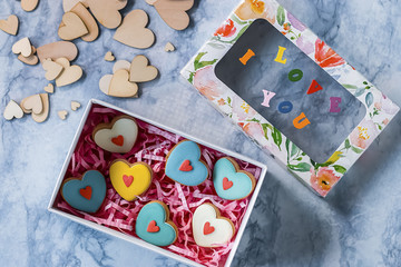 A decorative hearts and gingerbread with colorful glaze on a blue background. Valentine's Day.