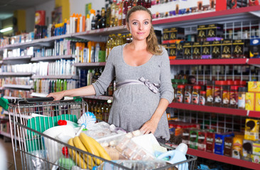 Portrait of pregnant female customer which is demonstrating purchases in trolley
