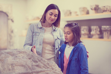 Mother and daughter regarding classical bas-reliefs
