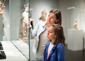 Mother and daughter regarding ancient statues