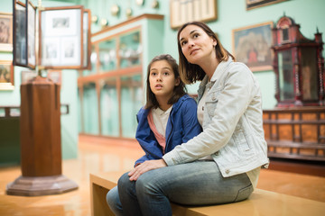 Young mom and daughter looking at expositions