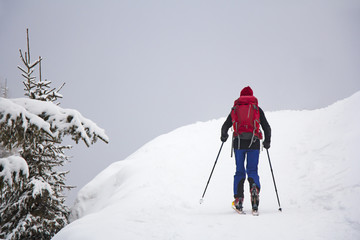 Man with skis walk by snow on the mountain