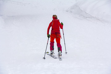 Woman with skis walk by snow on the mountain