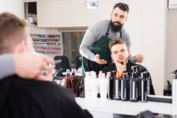 thoughtful guy stylist creating haircut for man client at hairdressing salon