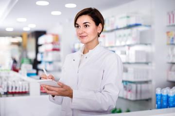 female pharmacist checking assortment of drugs in pharmacy