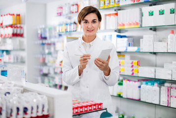 Female pharmacist noting assortment of drugs