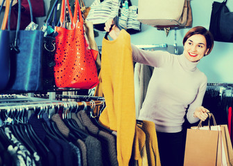 Female shopper examining warm sweaters in women's cloths shop