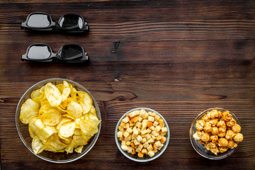 Cinema food. Crisp, popcorn, rusks near glasses on dark wooden background top view copy space