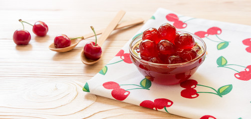 A bowl of sugared cherry fruits on a napkin with cherries, copy space.