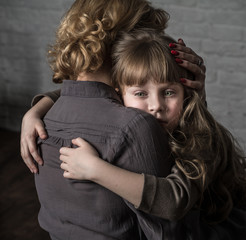 Photo shooting indoors. On the background of a white brick wall . Child ( girl ) hugs his mother.