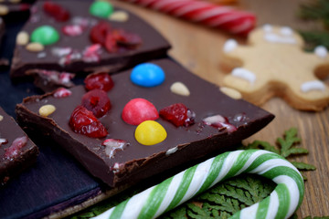 Dark chocolate bark with multicoloured drops, nuts and dried fruits broken into pieces