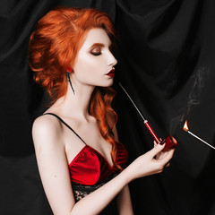 A red-haired woman with curly hair looks in a black corset and lingerie smokes a pipe on a black background. Conceptual photography