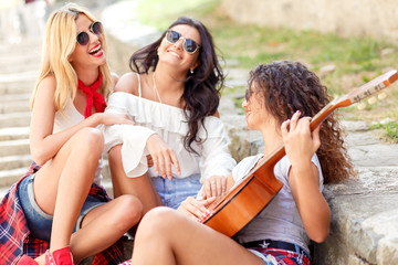 Group of young female friends sitting on the stairs singing and playing guitar.