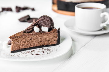 Chocolate cheesecake with pieces of chocolate, cookies and marshmallow on a white plate next to a cup of tea on the table