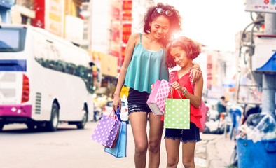 Young mother and child daughter shopping together walking on street market at sunset - Beautiful happy asian family holding shoppers looking at present standing in city road