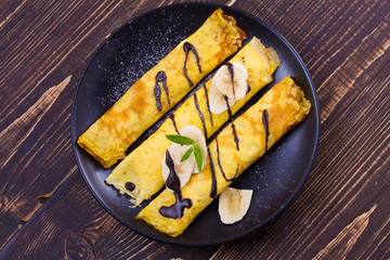 Home-made pancakes  filled with sweet white cheese, served with bananas, chocolate and mint. Wrapped pancakes. overhead, above, top view