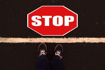 Sneakers near the white line and stop sign on the background of asphalt.