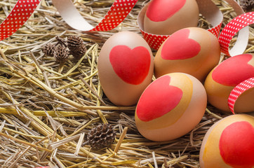 Egg with red heart on straw background