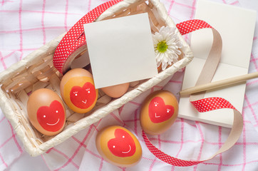 White paper note and egg with red heart on basket
