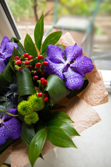 Decorative bouquet with purple orchids in kraft paper near the window