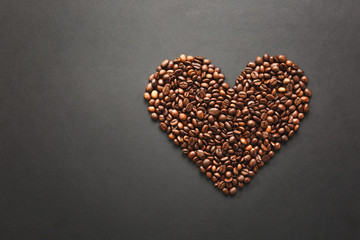 Brown coffee beans in form of heart isolated on black texture background for design. Saint Valentine's Day card on fabruary 14, holiday concept.