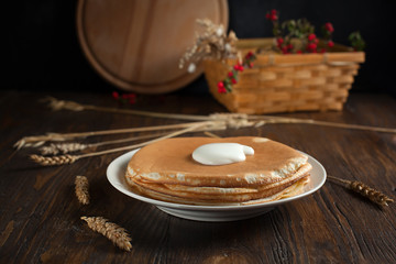 a pile of pancakes, berries, cookies, sour cream and a cutting board on parchment on a dark wooden table