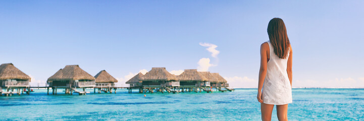 Wall Mural - Luxury travel Tahiti vacation tourist woman at overwater bungalows famous resort in French Polynesia. Girl at tropical holiday destination panoramic banner landscape background.