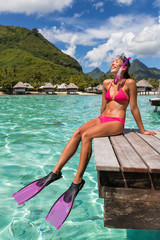 Wall Mural - Happy vacation snorkel girl relaxing at overwater bungalow balcony at luxury resort in tahiti. Snorkeling sport activity bikini woman sun tanning in beach paradise holiday. Travel lifestyle.