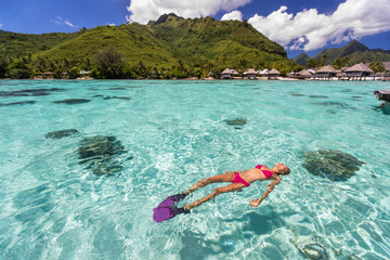 Wall Mural - Luxury paradise travel vacation bikini woman relaxing snorkeling in idyllic ocean coral reefs at luxury overwater bungalows resort in Tahiti. French polynesia cruise lifestyle. Holiday girl getaway.