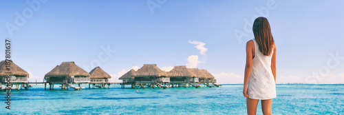 Wall mural Luxury travel Tahiti vacation tourist woman at overwater bungalows famous resort in French Polynesia. Girl at tropical holiday destination panoramic banner landscape background.