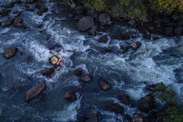Fotógrafo no meio de rápidos do rio Cubango visto do ar com drone na província do Huambo em Angola