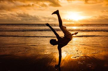 Rapaz a brincar ao pôr-do-sol na praia de Fútila em Cabinda, Angola