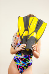 Woman covering her face with flippers having fun