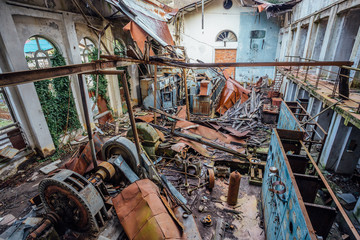 Ruined abandoned electrical substation. Rusty generator at machinery. Demolished roof
