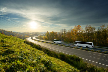 Fotobehang - White buses traveling on the highway turning towards the horizon in an autumn landscape at sunset