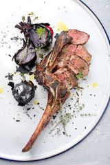 Barbecue dry aged wagyu caveman tomahawk steak sliced as close-up on a tray