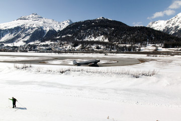 A view of a village in St Moritz, snow covered landscape and mountain, an airplane, a man skiing in the alps switzerland